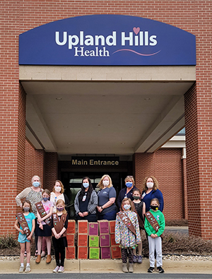 Girl Scout Troop pictured with Upland Hills Health nurses and donated cookies